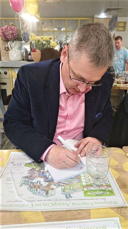 Дмитрий Моторин подписывает свою книгу читателю
